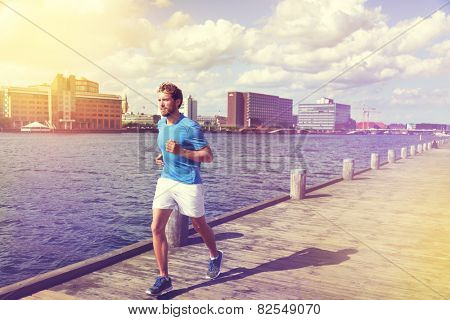 Urban man runner running in Copenhagen city, Denmark. Danish male adult jogging in Bryggen, Copenhagen, Scandinavian Europe.