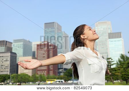 Freedom success businesswoman carefree in urban Tokyo, japanese city skyline - Success concept. Happy carefree business Asian woman arms open up in the sky, Japan.