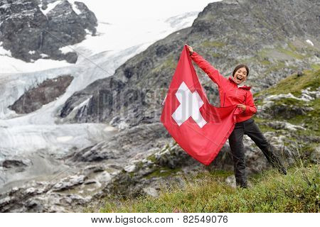 Switzerland hiker hiking cheering showing Swiss flag jumping in front of glacier. Happy Asian woman holding big red flag in nature.