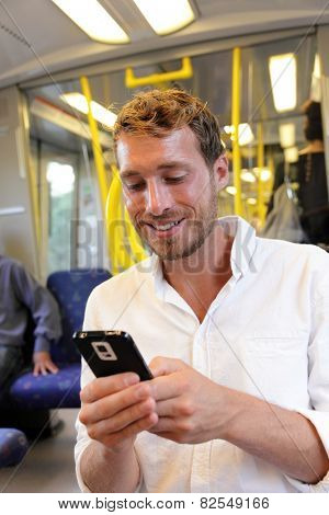 Subway businessman texting sms using smartphone apps. Casual man reading emails or news on smart phone online by 3g or 4g with wifi on swedish subway or outdoor train in Stockholm, Sweden.
