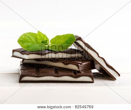 mint chocolate with mint leaves on a wooden background