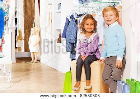 Boy stands and girl sits with shopping bags