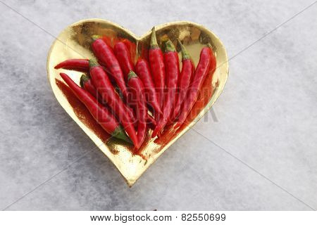red chili on the golden heart shape container