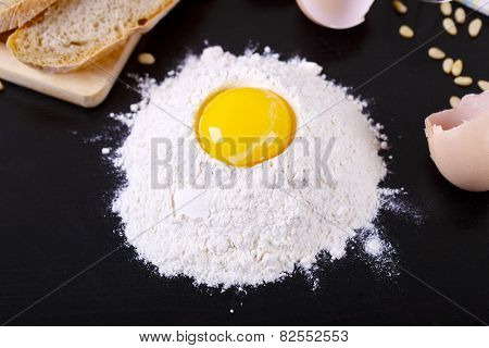 White flour and eggs isolated on black background