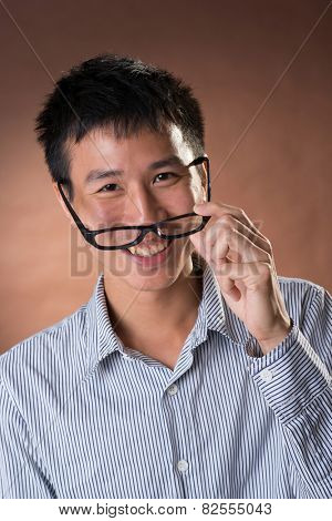 Young Chinese frank businessman, closeup portrait in studio.