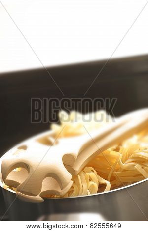 UNCOOKED PASTA AND TONGS