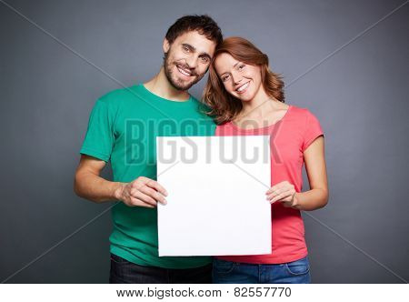 Amorous couple holding blank paper