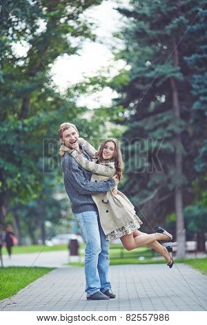 Happy guy holding his ecstatic girlfriend in park