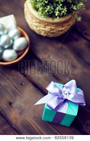 Small giftbox with violet ribbon and Easter eggs near by