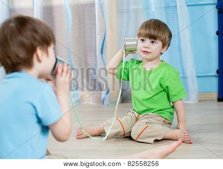 kids brothers talking with tin can telephone
