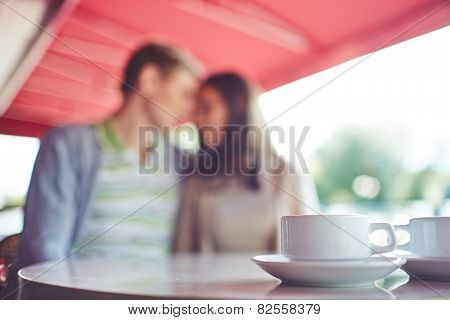 Porcelain cup with saucer on background of romantic couple