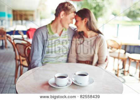 Porcelain cups with black coffee on background of affectionate valentines