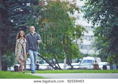 Young dates in casualwear walking in park