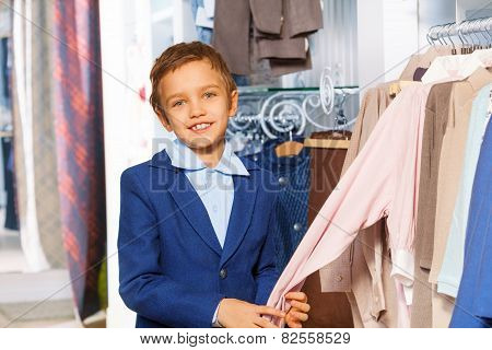 Small boy near clothes holding sweater's arm
