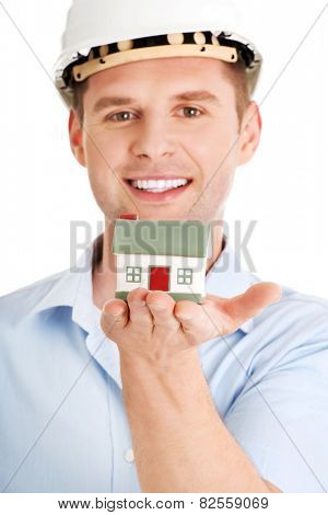 A forewoman holding a model house in hand