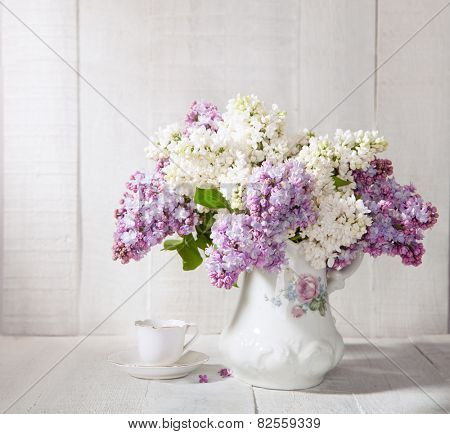 Lilac Bouquet  in old ceramic jug  and cup of coffee   against a white wooden table.