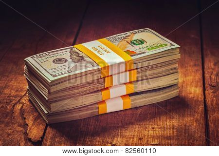Creative business finance making money concept - Vintage retro effect filtered hipster style image of stacks of new 100 US dollars 2013 edition banknotes (bills) bundles isolated on wooden background