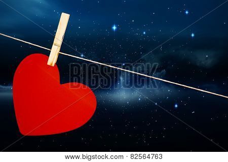 Heart hanging on line against stars twinkling in night sky