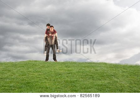 Man giving girlfriend piggy back against cloudy sky