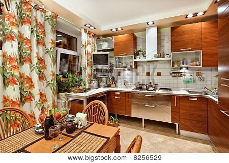 Kitchen Interior With Wooden Furniture, Table And Many Utensils