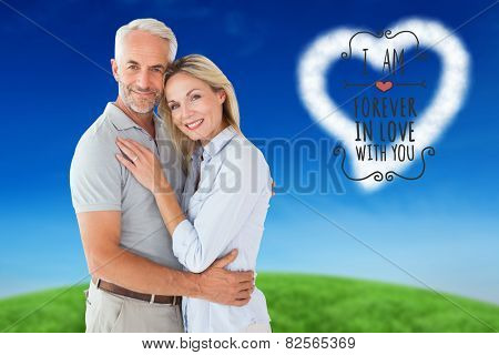 Happy couple standing and smiling at camera against green hill under blue sky