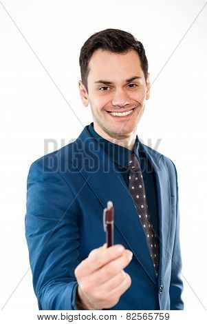 Businessman holding / offering a pen in his hand isolated over white background.