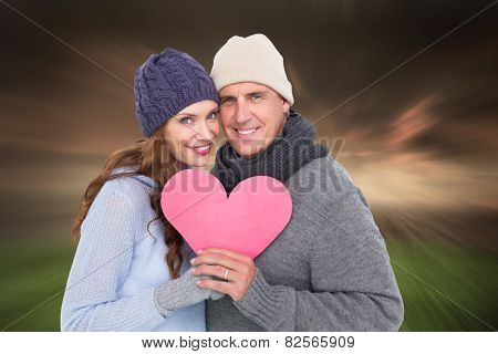 Happy couple in warm clothing holding heart against stormy sky over city