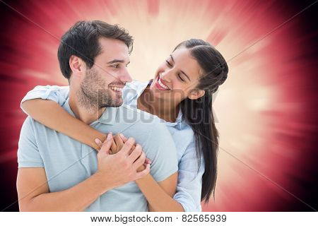 Cute couple smiling at each other against valentines heart design