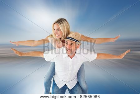 Happy man giving his partner a piggy back against room with large window looking on city