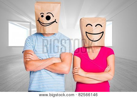 Young couple with bags over heads against bright white room with opened windows
