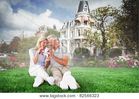 Happy couple sitting and holding present against sunny day by the river