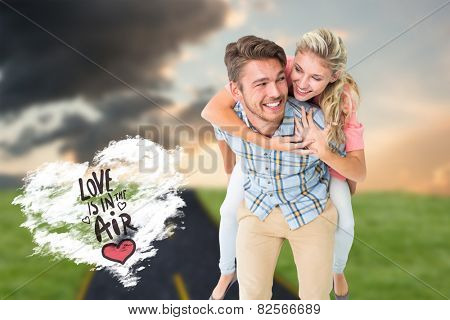 Handsome man giving piggy back to his girlfriend against cloud heart