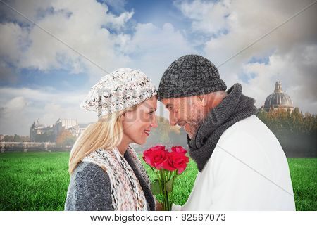 Smiling couple in winter fashion posing with roses against paris under cloudy sky