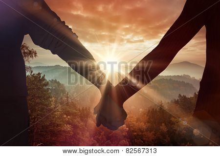 Couple holding hands rear view against sunrise over mountains