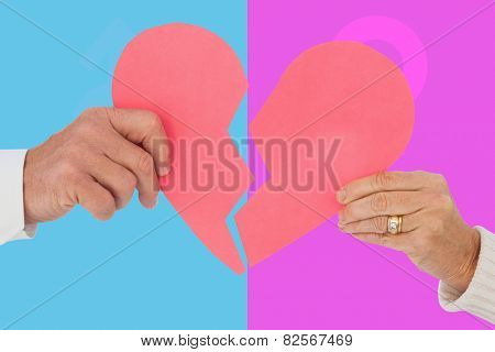 Couple holding a broken paper heart against pink and blue