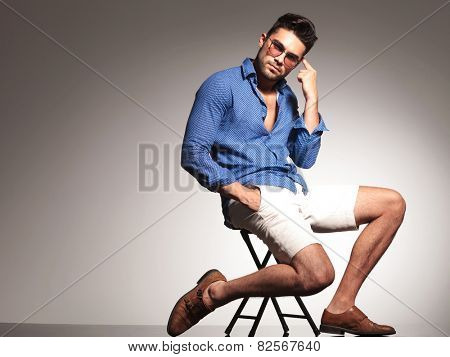 Handsome young fashion man pointing to his head while sitting on a chiar with his hand in pocket.