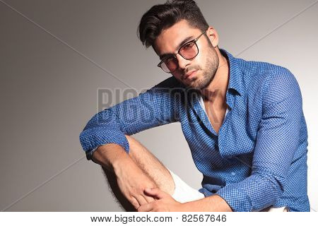 Portrait of a attractive young fashion man resting his hand on his knee while looking at the camera.