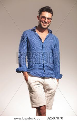 Picture of a handsome young fashion man smiling to the camera with both hands in his pocket.