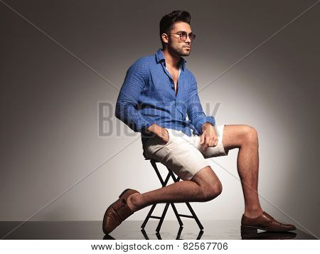 Attractive young fashion man sitting on a chair, holding one hand in his pocket while looking away from the camera.