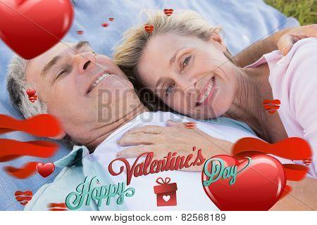 Happy senior couple cuddling on blanket against cute valentines message