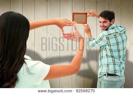 Happy young couple putting up picture frame against wooden planks