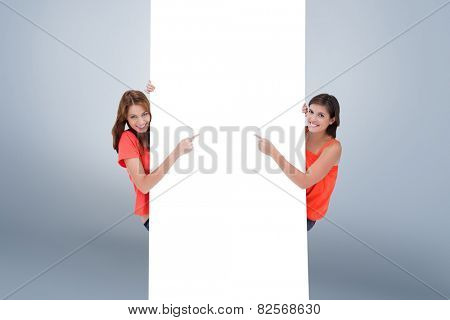 Teenage girls looking at the camera while pointing their fingers on a blank poster against grey vignette