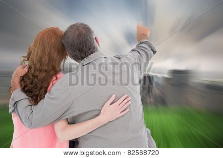 Casual couple pointing and looking against cloudy sky over city