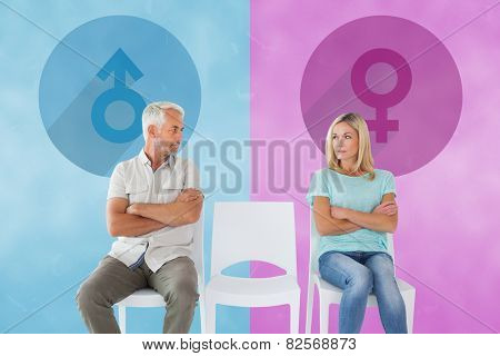 Unhappy couple not speaking to each other against pink and blue