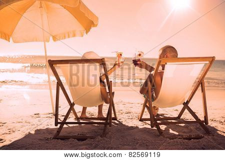 Happy couple on the beach drinking cocktails while relaxing on their deck chairs