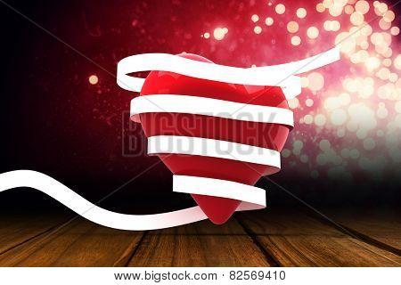Love heart wrapped in ribbon against shimmering light design over boards
