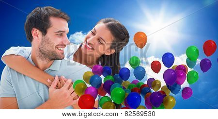 Cute couple smiling at each other against bright blue sky with clouds