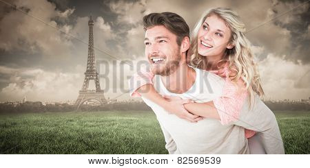 Handsome man giving piggy back to his girlfriend against paris under cloudy sky