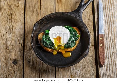 Bruschetta with spinach and poached egg in a frying pan