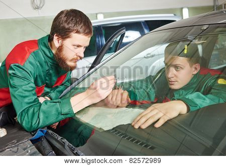 Automobile glazier repairman teaching or discussing with partner windscreen repair of a car in auto service station garage